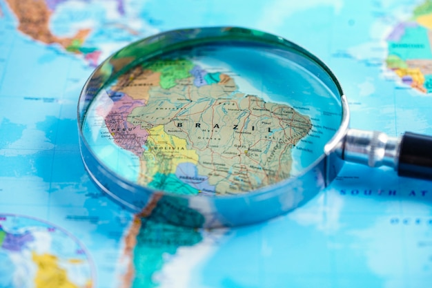 Brazil : magnifying glass with world glove map. Premium Photo