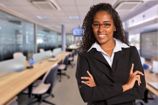흐리게 사무실 공간에 카메라를보고 브라질 흑인 비즈니스 여자. 공간을 복사하십시오. 프리미엄 사진