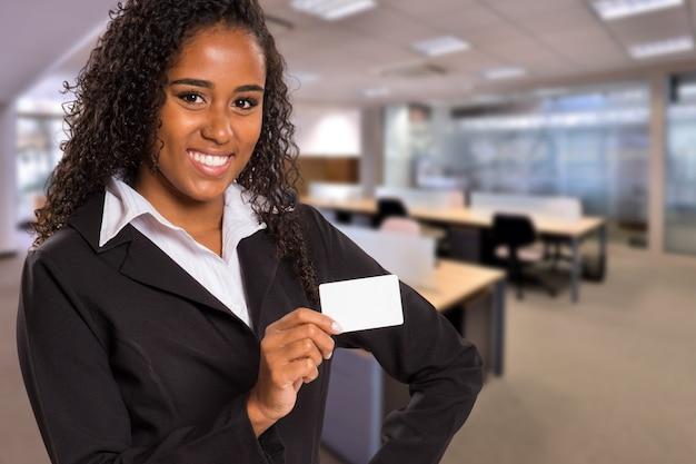 흐리게 사무실 공간에 카메라를보고 손에 흰색 카드와 브라질 흑인 비즈니스 여자. 공간을 복사하십시오. 프리미엄 사진