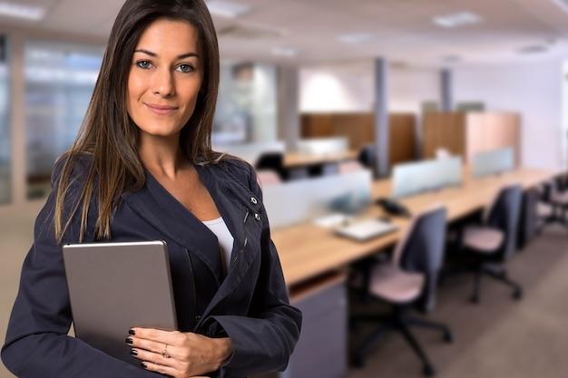 흐릿한 사무실 공간에서 카메라를보고 태블릿 브라질 비즈니스 여자. 공간을 복사하십시오. 프리미엄 사진