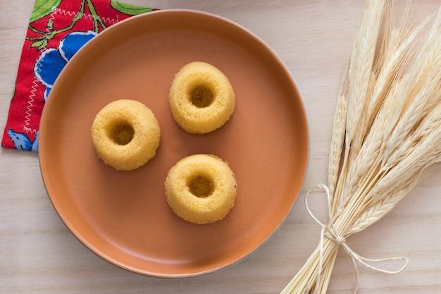 Brazilian culture. mini cornmeal cake on a beautiful rustic plate and wheat Premium Photo