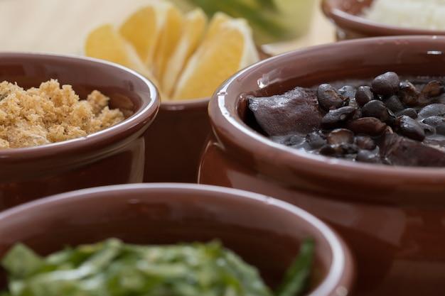 Brazilian feijoada, farofa, collard greens and orange Premium Photo