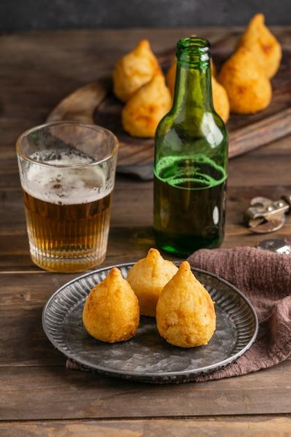 Бразильская еда на тарелке и пивном бокале под высоким углом Бесплатные Фотографии