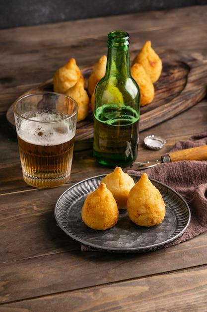 Cibo brasiliano su piastra e bicchiere di birra Foto Gratuite