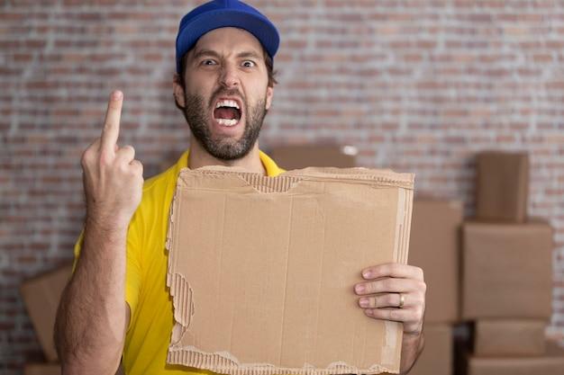 ブラジルの郵便配達員が、たくさんの箱のある預金に空白のボードを持っています。コピースペース。 Premium写真