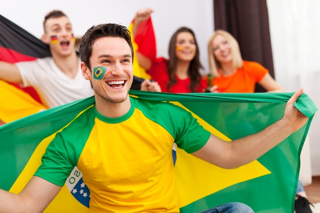 Brazilian man with friends from different country enjoying the soccer on tv Free Photo