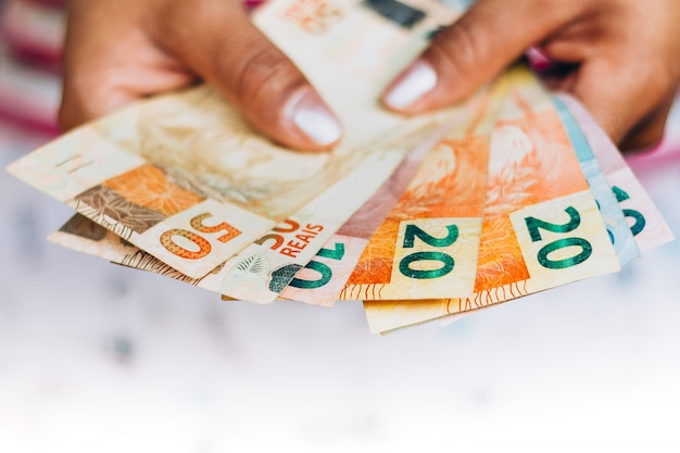 Brazilian money - real notes - brazilian currency - finance concept - investments - wealth - woman holding money. Premium Photo