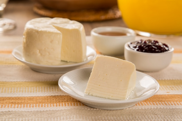 Brazilian sheep cheese. bread, fruits and different types of cheese in the background. Premium Photo