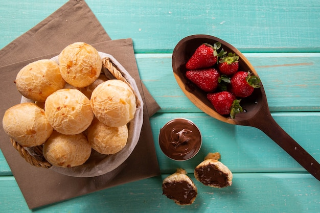 Brazilian snack cheese bread stuffed with chocolate and strawberry fruit on green wood background. Premium Photo