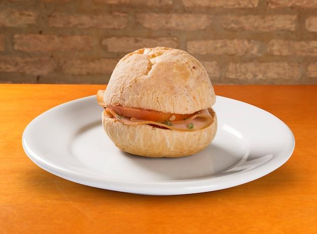 Brazilian snack pao de queijo (cheese bread) on white plate with cheese, ham, butter Premium Photo