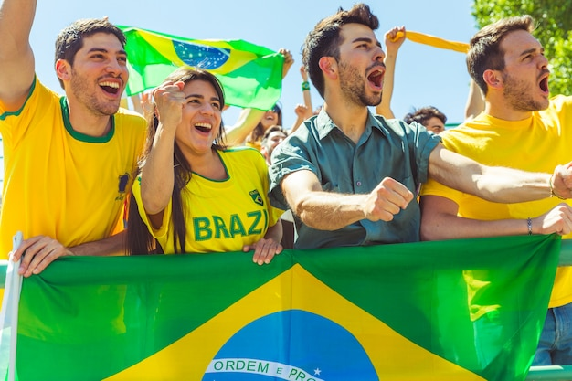 Brazilian supporters celebrating at stadium with flags Premium Photo
