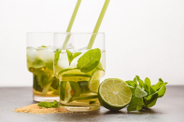Brazilian traditional caipirinha with lime, sugar and mint in glasses. white background, dark table, copy space. Premium Photo