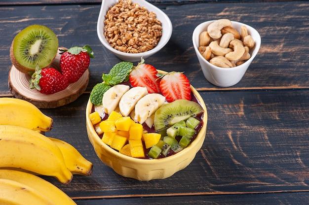 Бразильский йогурт в миске в сопровождении тропических фруктов. копировать пространство Premium Фотографии