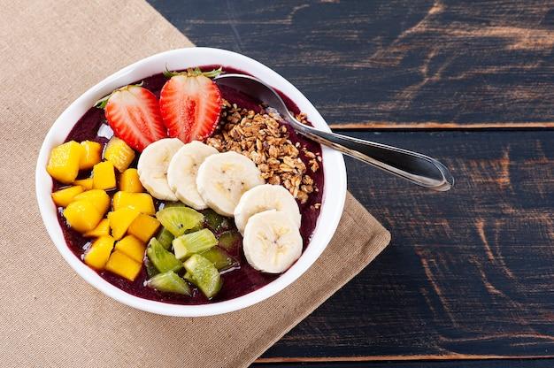 Бразильский йогурт в миске в сопровождении тропических фруктов Premium Фотографии