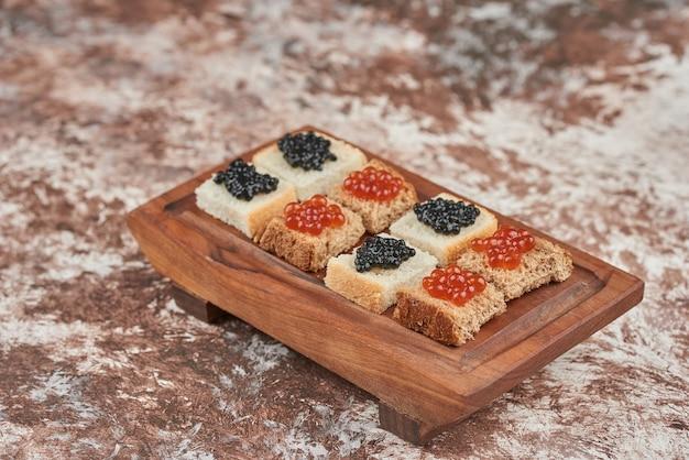 나무 보드에 캐 비어와 대리석에 빵 식 전주. 무료 사진