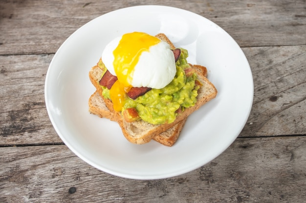 Bread, avocado sauce, bacon, spinach, egg benedict on white plate and old wood background Premium Photo