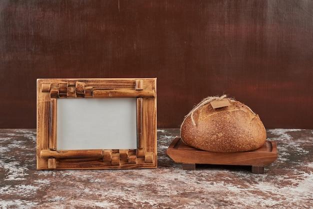 Bread bun on marble on wooden board. Free Photo