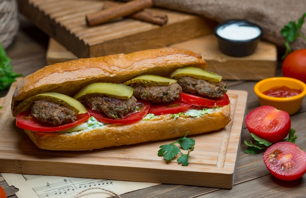 A bread bun stuffed with meat balls, green bell pepper , tomato slices and sandwich dip sauce Free Photo