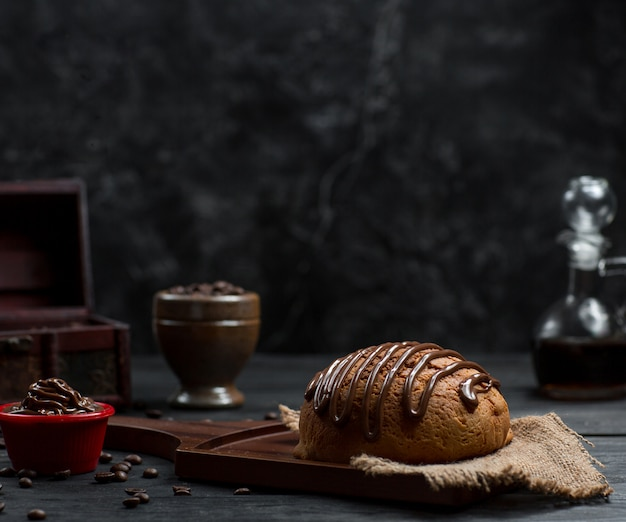 Bread bun with choco sauce on the top and chocolate mousse Free Photo