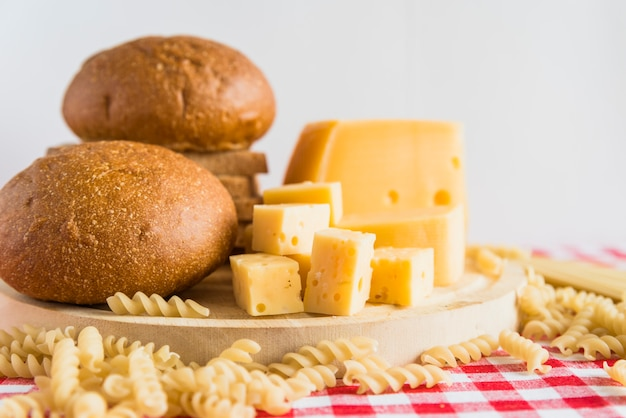 Bread and cheese on plate near scattered pasta Free Photo