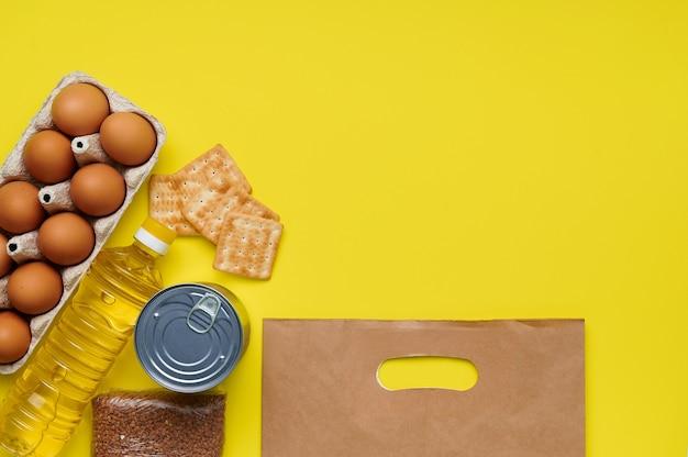 パン粉、ビスケット、ソバ、卵、缶詰、黄色の背景にひまわり油紙袋 Premium写真