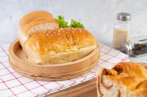 Хлеб в деревянном подносе на красной и белой ткани. Бесплатные Фотографии