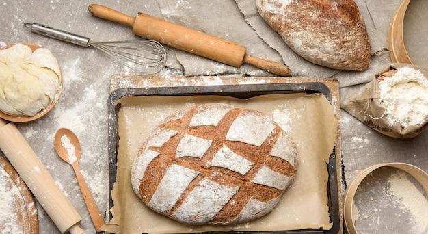 Хлеб, замешанное тесто из белой пшеничной муки лежит на деревянной тарелке и деревянной скалке, вид сверху Premium Фотографии