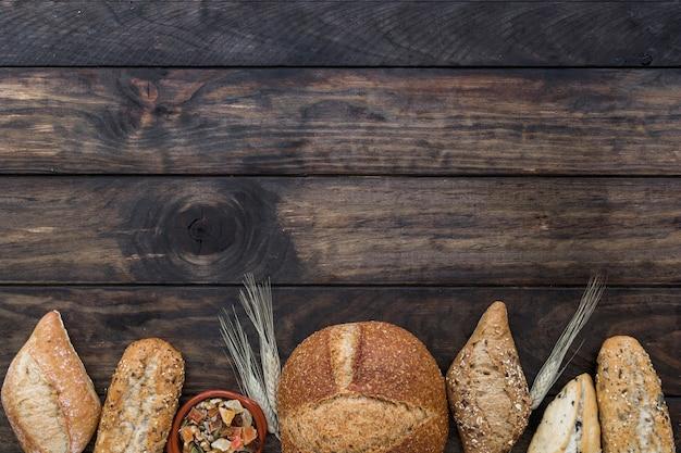 Pagnotte di pane con piastra sul tavolo di legno Foto Gratuite