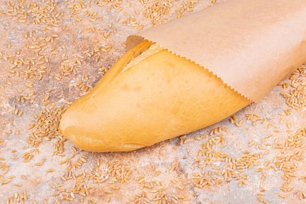 Pane in un sacchetto di carta accanto al chicco di grano cosparso, sul tavolo di marmo. Foto Gratuite
