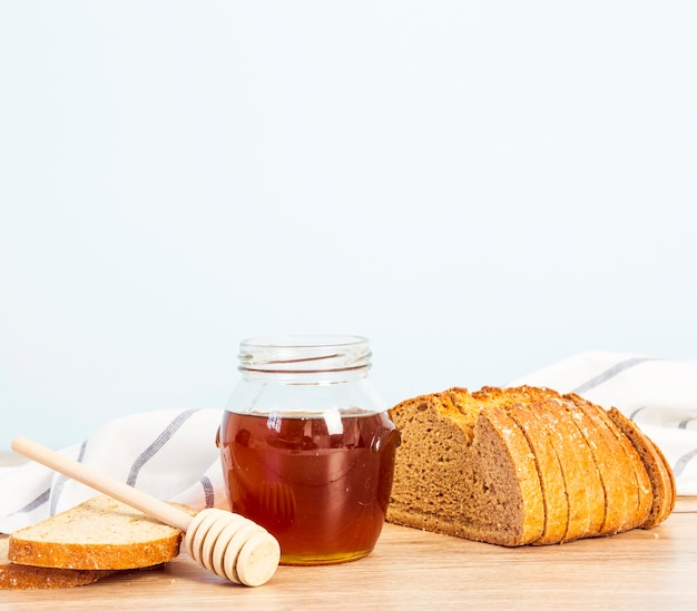 Bread slice and jar of honey for breakfast over wooden desk Free Photo
