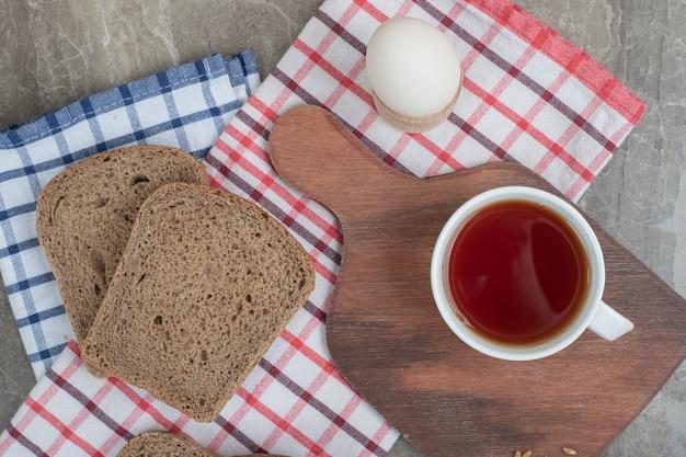 卵とテーブルクロスの上のパンのスライスとお茶のカップ。高品質の写真 無料写真