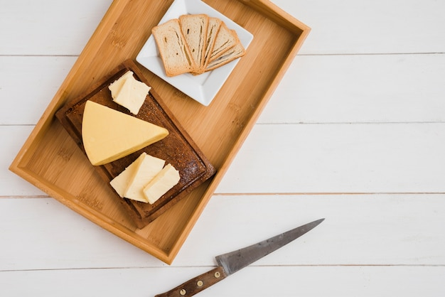 Bread slices and cheese wedges on wooden tray with knife Free Photo