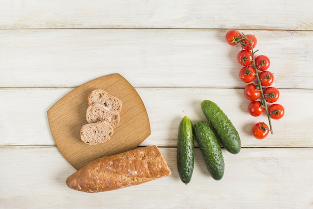 Bread slices; cucumber and red cherry tomatoes on wooden table Free Photo