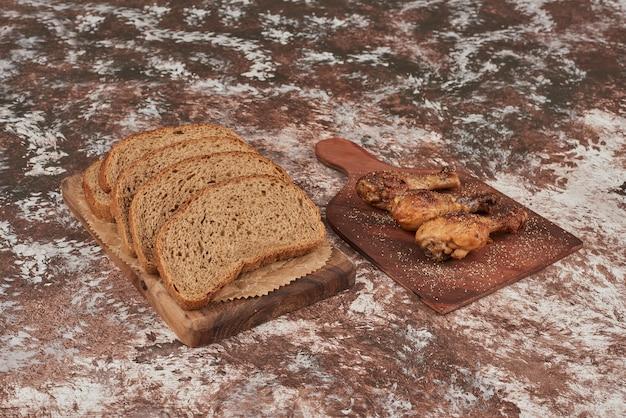 Fette di pane su marmo con cosce di pollo. Foto Gratuite