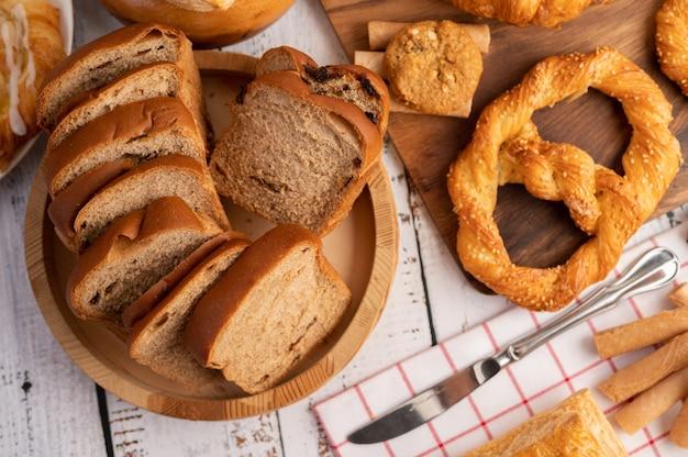Ломтики хлеба размещены в деревянной тарелке на белом деревянном столе. Бесплатные Фотографии