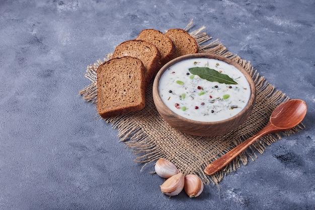 ヨーグルトスープとニンニクのカップでパンのスライス。 無料写真