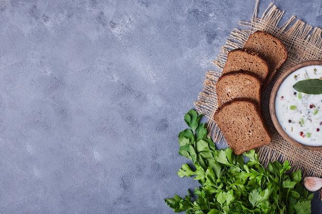 ヨーグルトスープ、パセリ、ニンニクのカップでパンのスライス。 無料写真