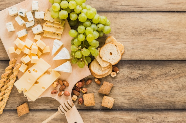 Bread sticks, cheese blocks, grapes, bread and cookies on wooden desk Free Photo