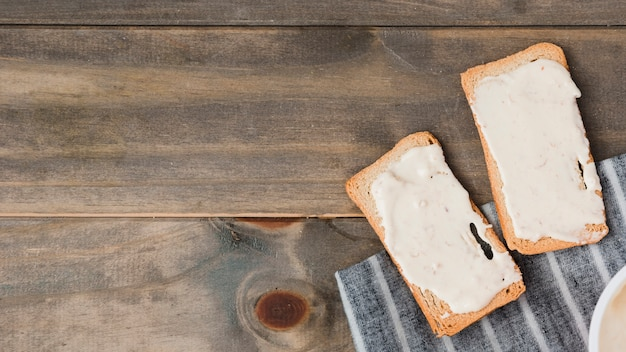Bread toast with cheese spread on wooden table Free Photo