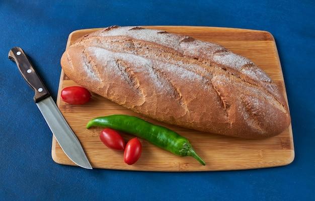 Хлеб, помидоры, перец чили и нож лежат на разделочной доске, малая глубина резкости, натюрморт Premium Фотографии