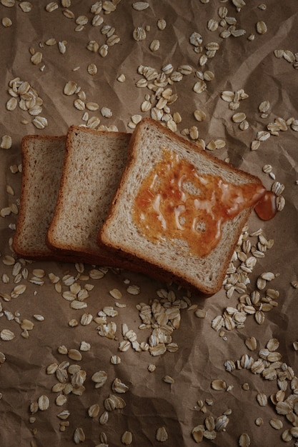 Bread with jam on a brown space and oatmeal Premium Photo