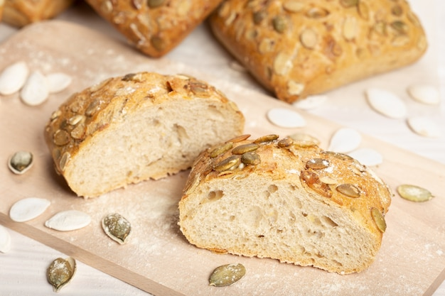 Bread with pumpkin seeds on cutting board Premium Photo