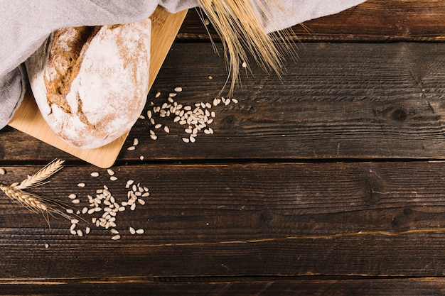 Bread with sunflower seeds and wheat crop on wooden table Free Photo