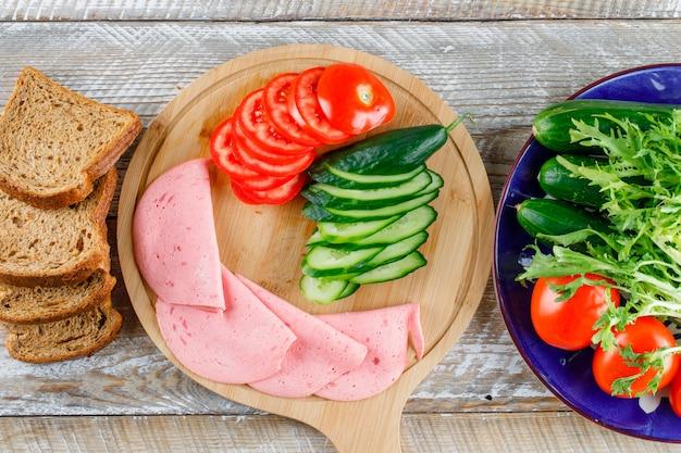 Хлеб с помидорами, огурцами, колбасой, зеленью на деревянной доске и разделочной доской Бесплатные Фотографии