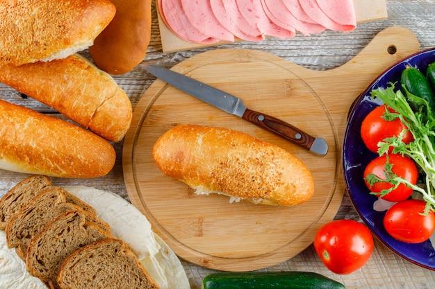 Хлеб с помидорами, огурцами, ножом, колбасой, зеленью плоско положите на деревянные и разделочную доску Бесплатные Фотографии