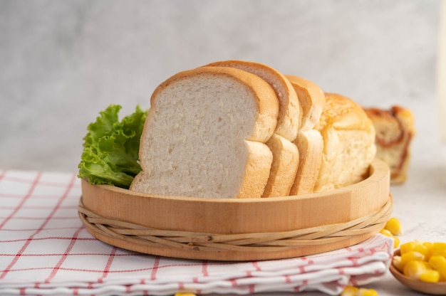 Bread in a wooden tray on a red and white cloth. Free Photo