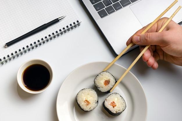 Break time for sushi eating. sushi rolls snacking at work. Premium Photo