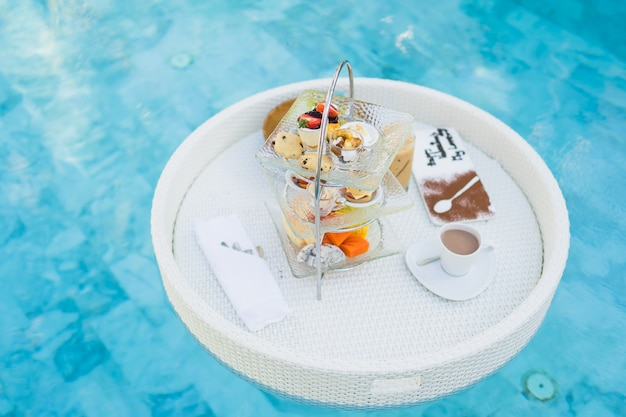 Breakfast and afternoon tea set floating around swimming pool Free Photo