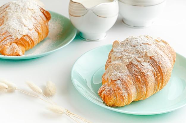 朝食ベーカリー、粉砂糖とアーモンドフレークと白い背景のクロワッサン。閉じる。 Premium写真