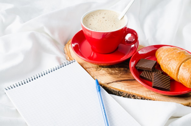 Breakfast in bed and empty notebook for note. Premium Photo